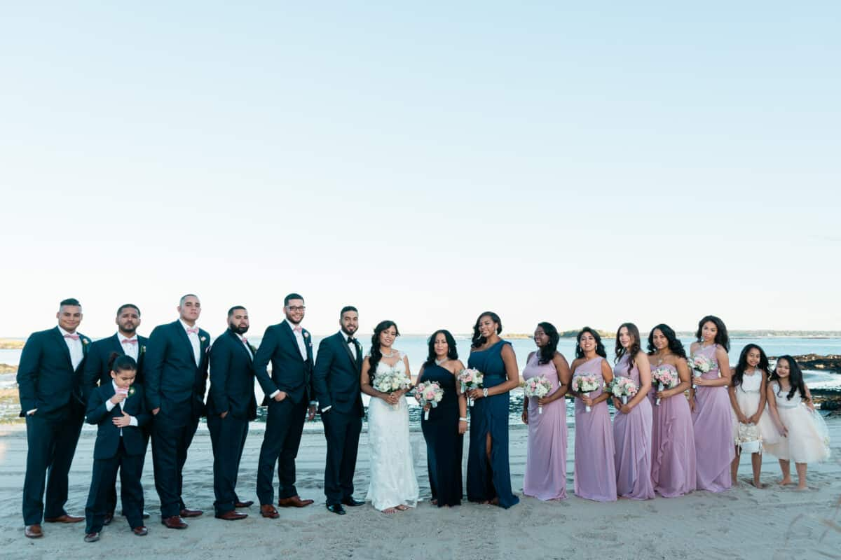 Bride groom and wedding party poses for photo on beach before a Hudson Valley Wedding at Green Tree Country Club in New Rochelle