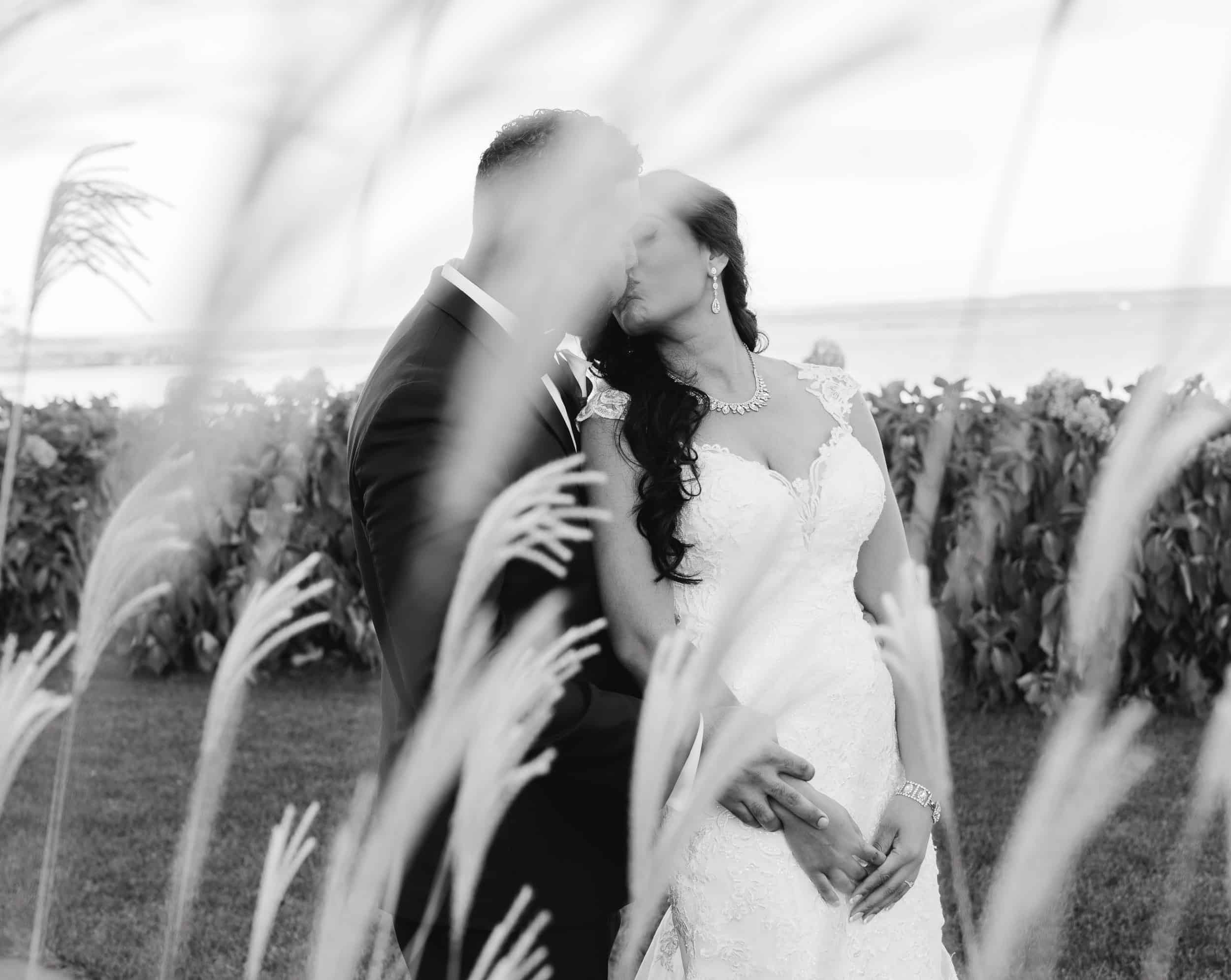 Black and White photo of bride and groom in flowers at Hudson Valley Wedding at Green Tree Country Club in New Rochelle