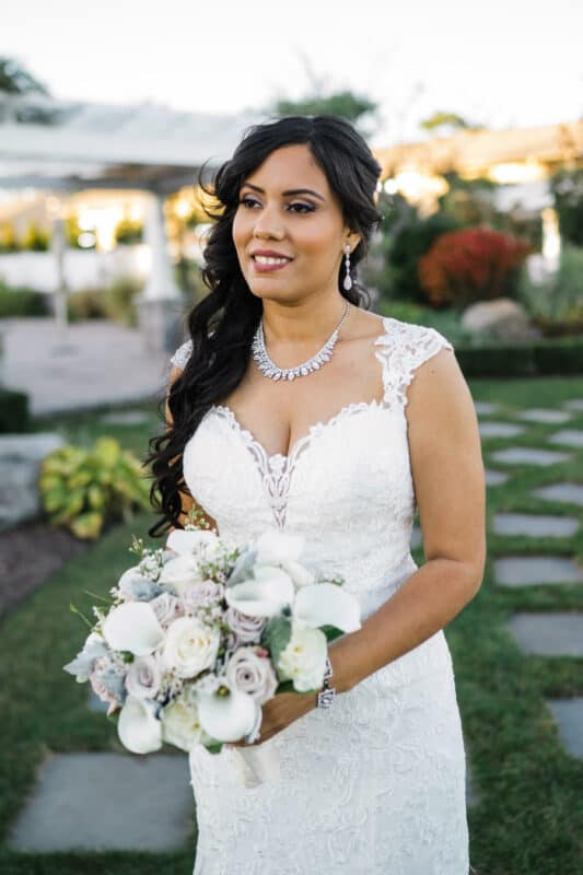 Bride poses with bouquet in Garden before a Hudson Valley Wedding at Green Tree Country Club in New Rochelle