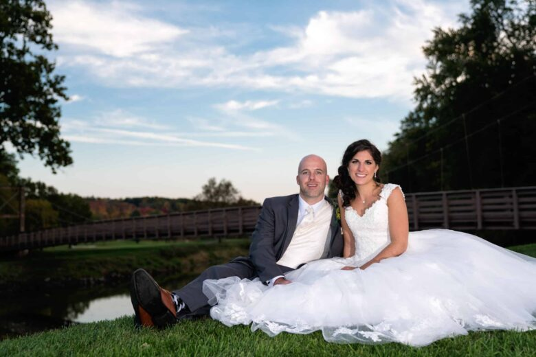 Bride and Groom lay on the grass by a bridge at a Hudson Valley Wedding At West Hills Country Club In Middletown, New York