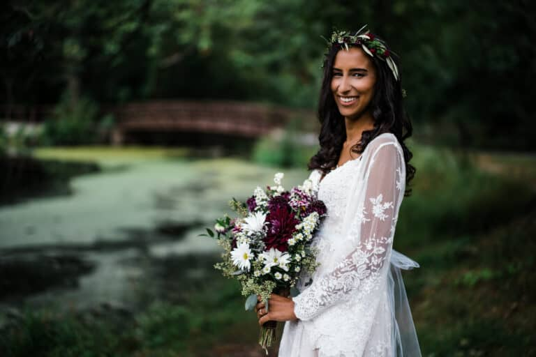 Bride poses with flowers by a bridge before her Hudson Valley wedding