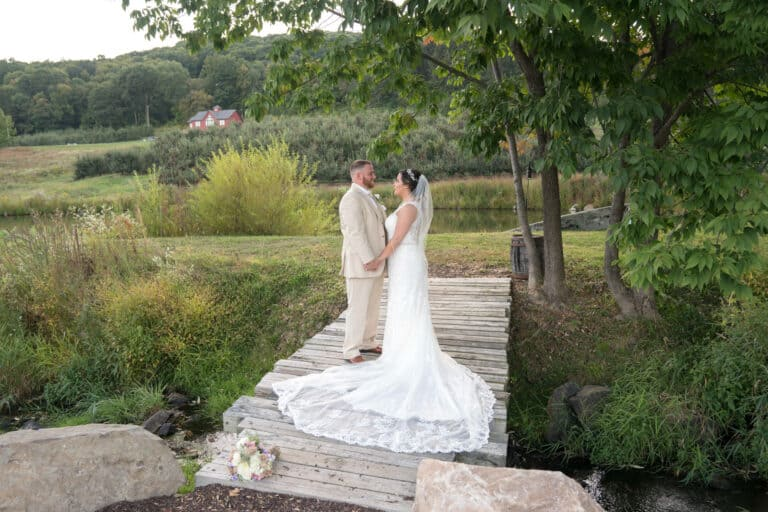 Bride and groom hold hands on bridge at Hudson Valley Wedding at Nostranos Vineyard