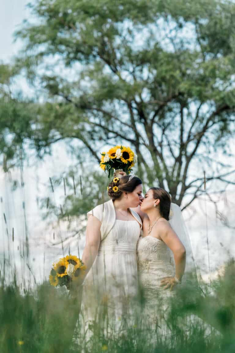 Bride and bride kissing in field at Hudson Valley same sex wedding At Lippincott Manor in Walkill New York