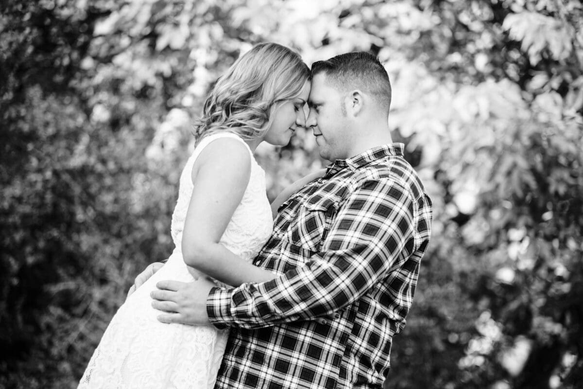 Bride and groom touches forehead at a farm engagement shoot