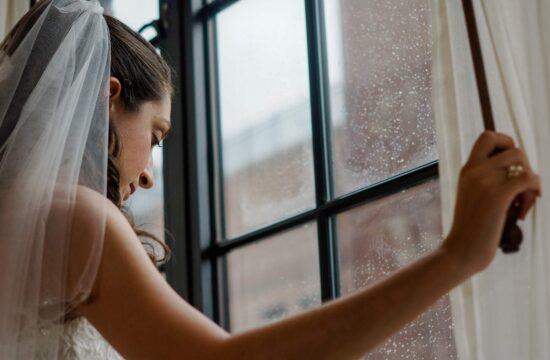 Bride Holds cord and look out window before a Torch Club Wedding in New York City