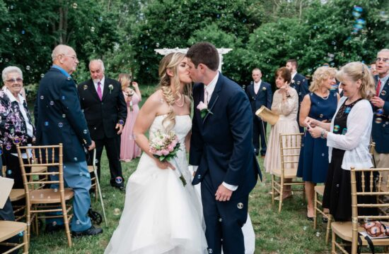 Groom kisses bride surrounded by bubbles during ceremony at a Palacios Wedding in the Hudson Valley