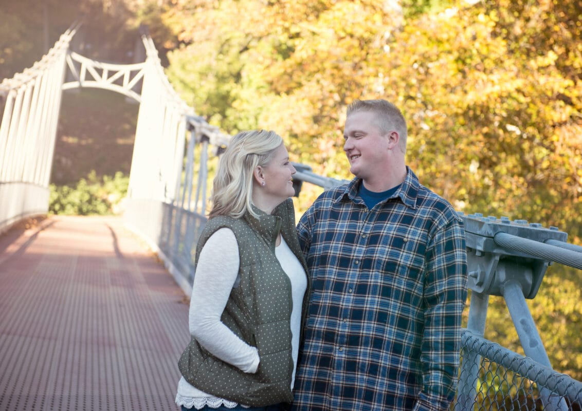 Bride and Groom hug and look into each others eyes for a photo on a Bridge for a Hudson Valley Engagement Photo