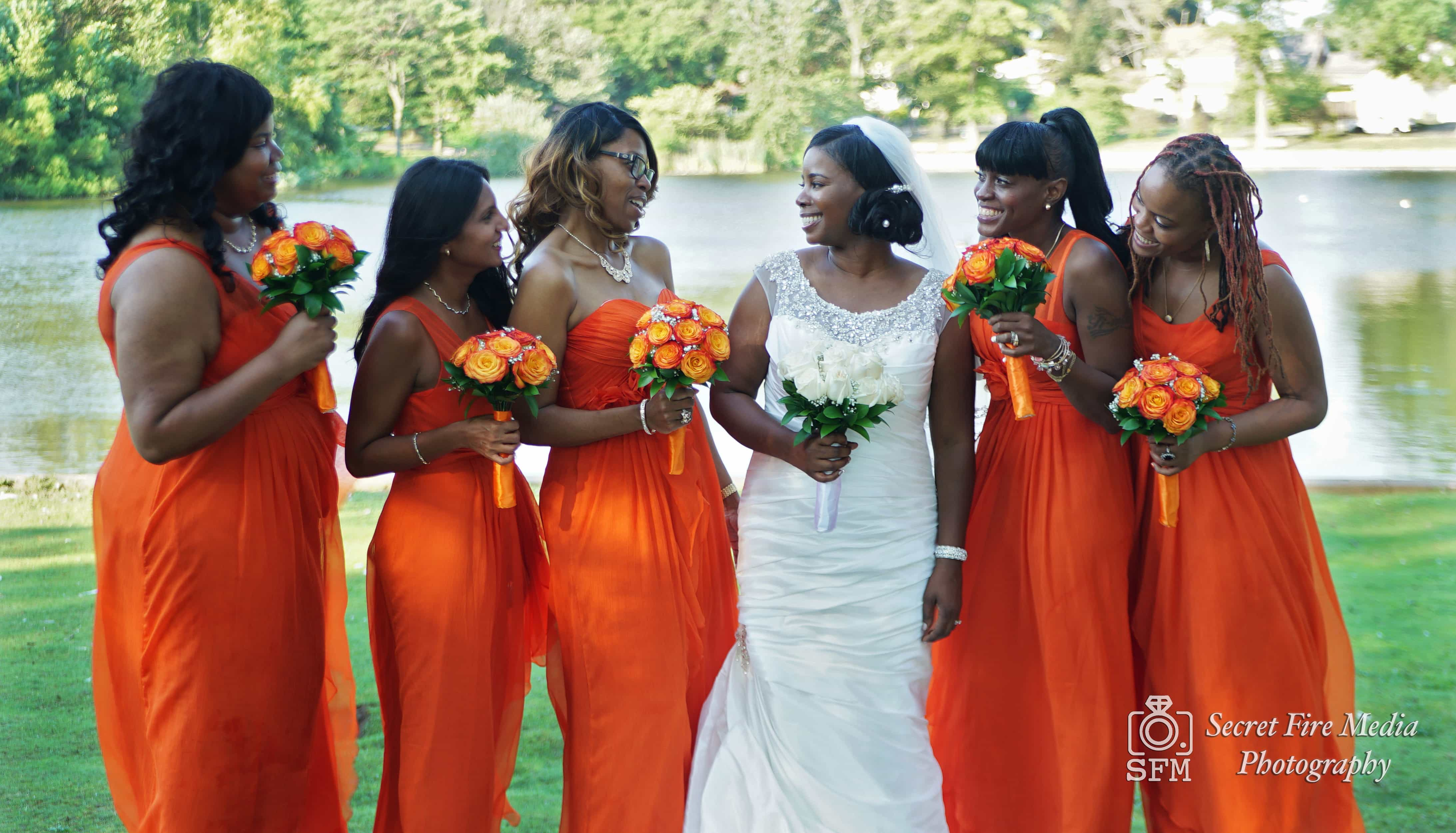 poses with bridesmaids by a lake before a Chateau Briand Wedding in Long Island