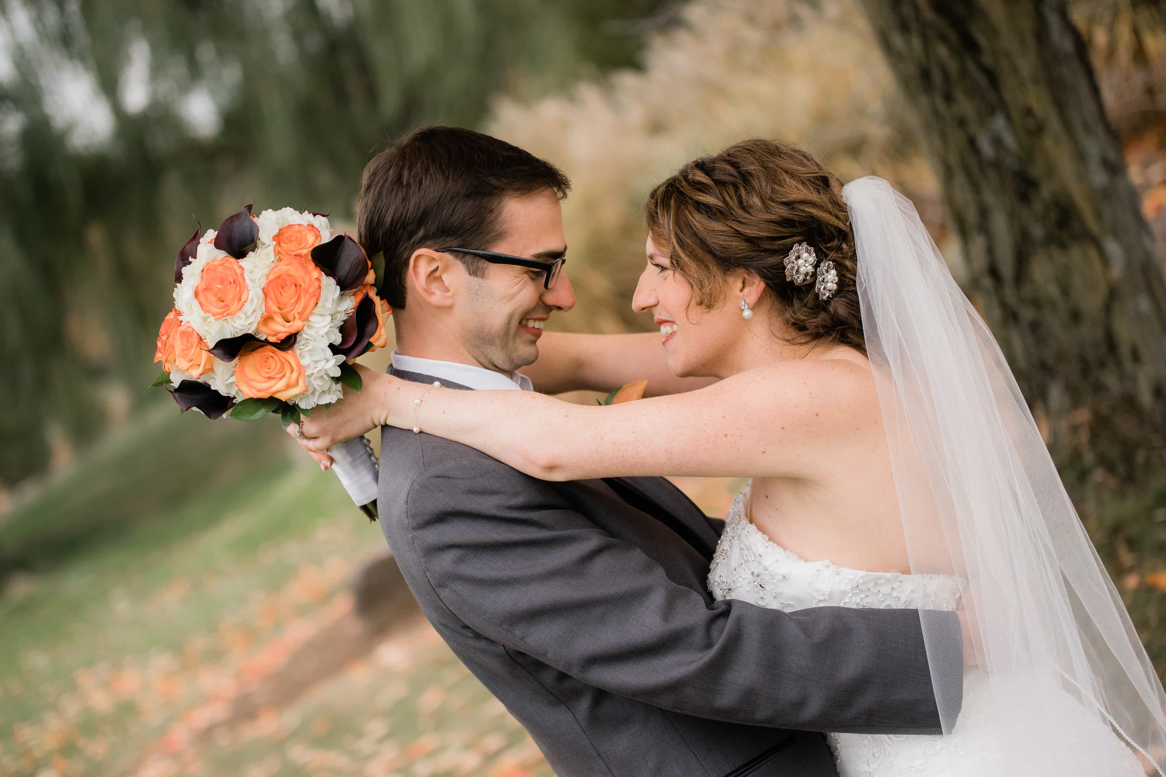 Bride and Groom hug by tree at a Hudson Valley Wedding at New York Country Club