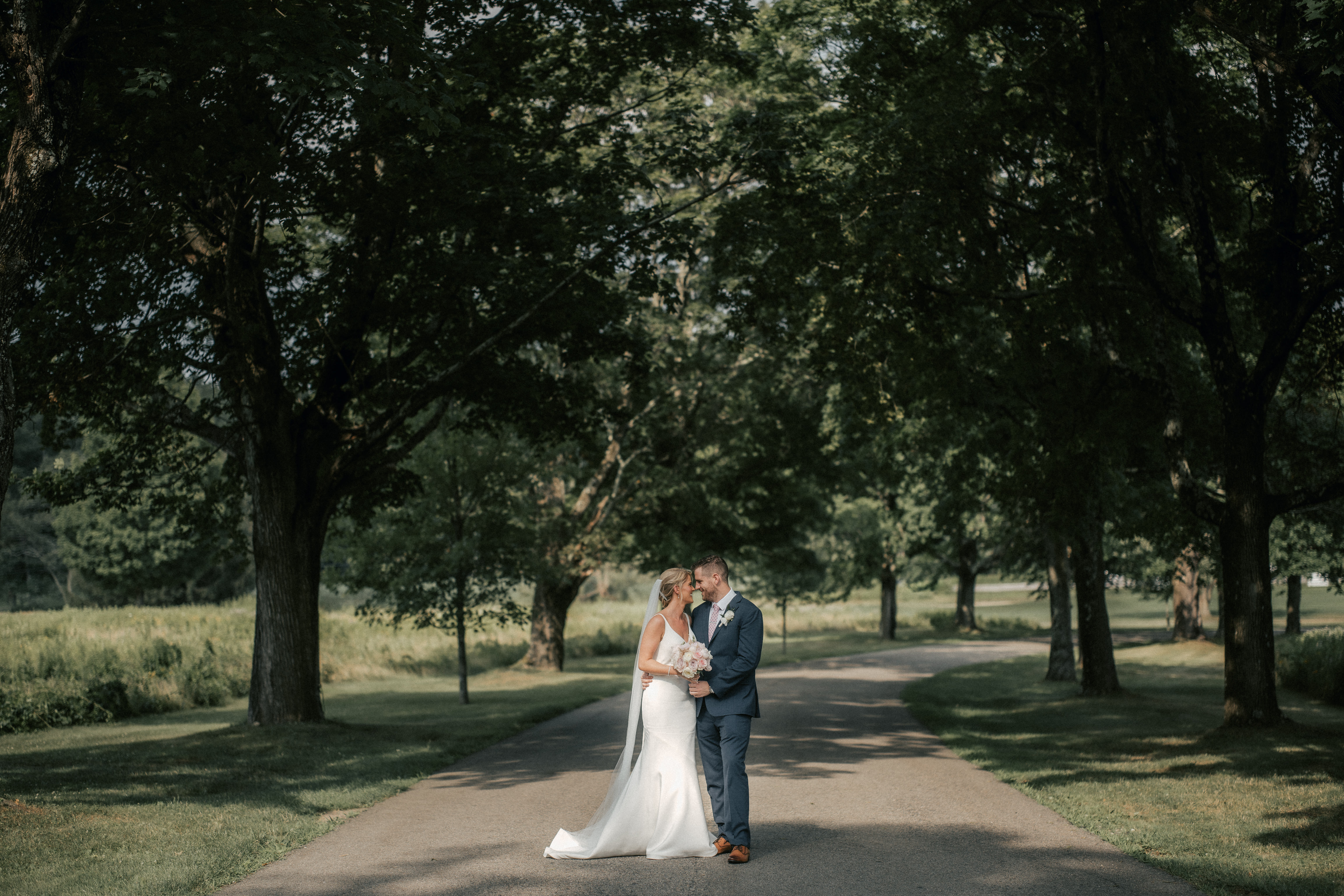 Bride and Groom pose and smile for a photo on forest road at a Hudson Valley wedding at The Garrison