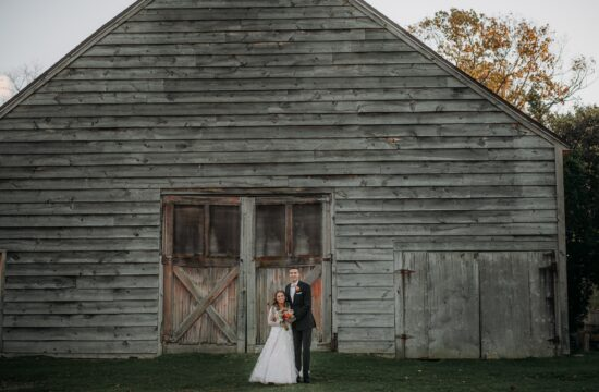 Bride and Groom pose for a photo by a red wooden barn at a wedding at Highlands Country Club