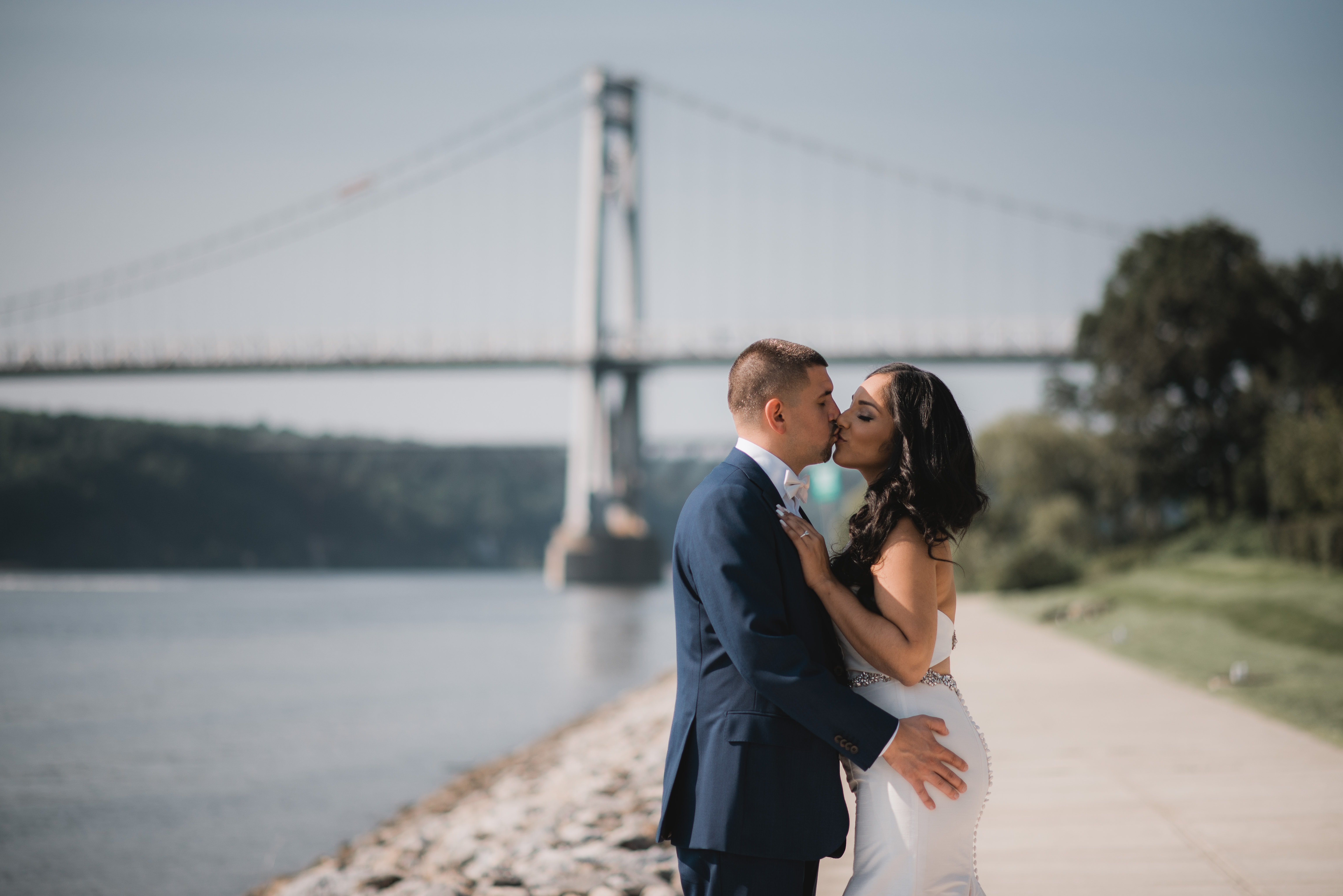 Bride poses by bridge on hudson river at a Hudson Valley Wedding at The Grandview in Poughkeepsie