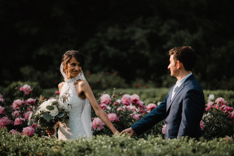 Bride walks with groom in flower garden at a Hudson Valley Wedding at Locust Grove Estate