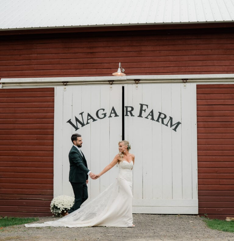 Bride and Groom hold hands by a barn at a Wedding at the Wager House for Wager House Wedding Photos