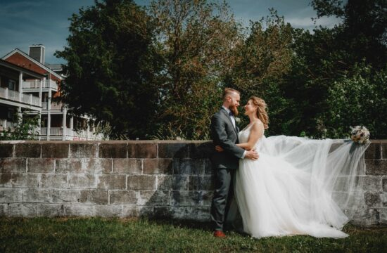 Bride and Groom pose by wall at a Hudson Valley Wedding at Chalet on the Hudson