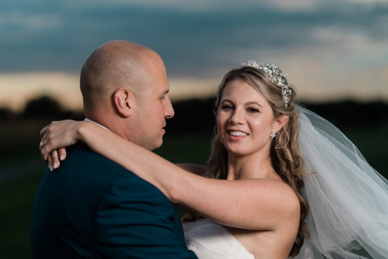 Bride smiles for a photo at sunset at a Hudson Valley Wedding at Links at Union Vale