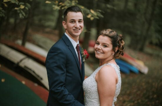 Bride and groom pose for photo along path of boats at a Hudson Valley Wedding at Sedgewick Golf Club