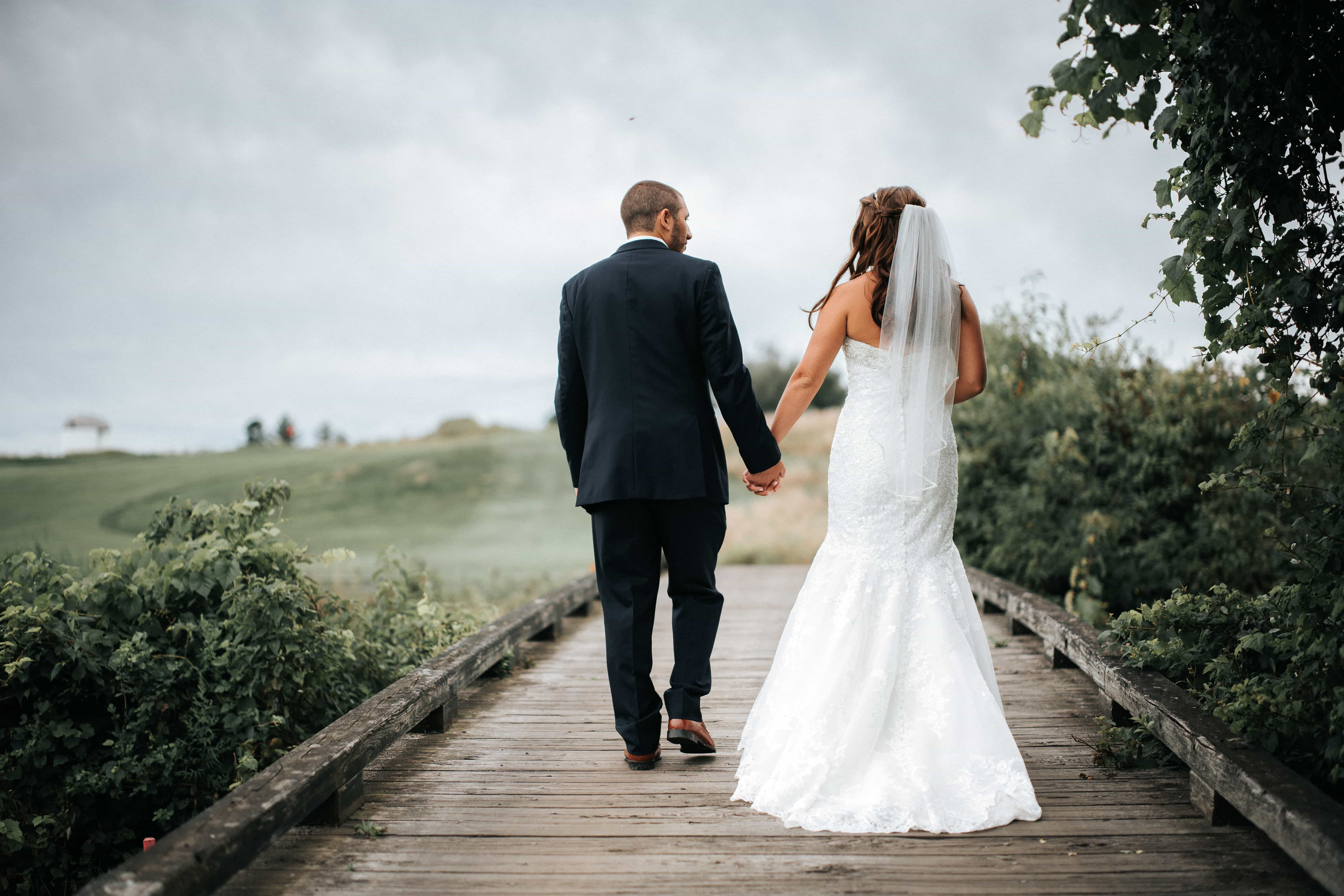Bride and Groom hold hands and walk on a wooden bridge at a wedding at Links at Union Vale