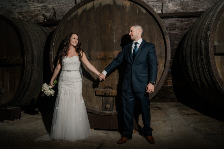 Bride and Groom pose by wine barrels at a Hudson Valley Wedding at the Brotherhood Winery