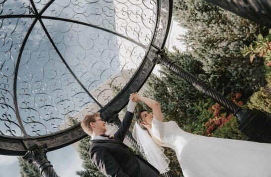 Groom twirls Bride in metal arbor at a Hudson Valley Wedding at Antonys Pier 9