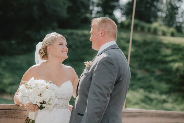 Bride looks into grooms eyes on a metal bridge at a Hudson Valley Wedding at West Hills Country Club