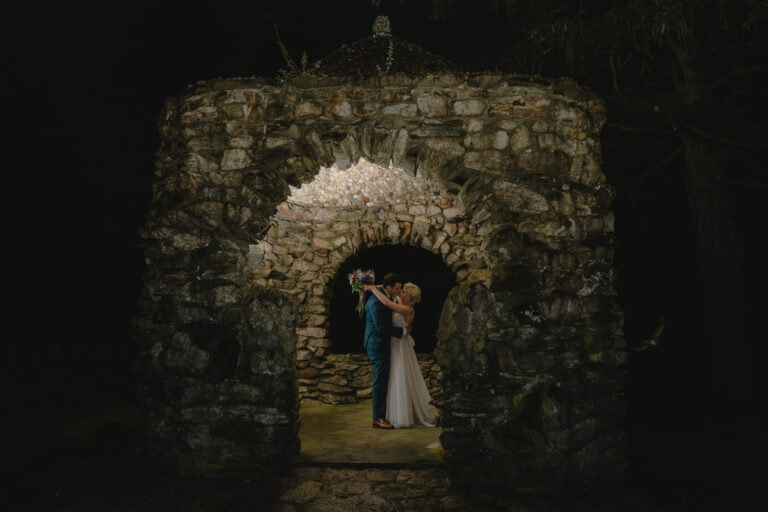 Bride and Groom kiss under stone arbor at a Hudson Valley Wedding at The Garrison