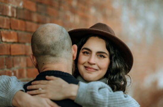 Bride land groom hug by brick wall at Vanderbilt Estate for Hudson Valley Engagement Photography
